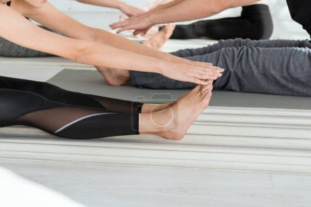 Foto de La vista recortada de los jóvenes practicando yoga en la curva hacia delante sentados posan. - Imagen libre de derechos