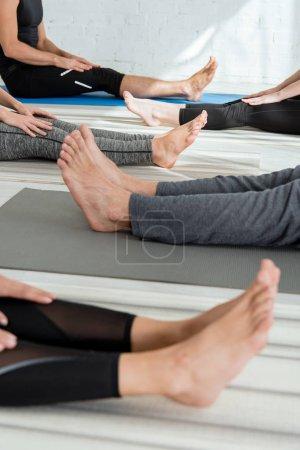 Photo pour Vue dégagée de personnes pieds nus assises sur des tapis de yoga dans le personnel pose - image libre de droit