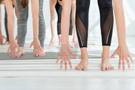 Photo pour Vue recadrée des personnes pieds nus pratiquant la pose de levage à mi-chemin - image libre de droit