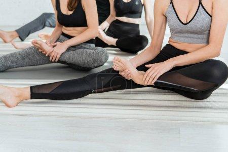 Photo pour Crochet vue de jeunes femmes pratiquant le yoga dans une pose d'étirement de jambe - image libre de droit