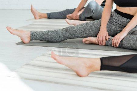 Photo pour Crochet vue des femmes et de l'homme s'entraînant à étirer la jambe pose - image libre de droit