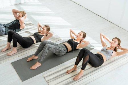 Photo pour Vue à angle droit de jeunes pratiquant le yoga lors de séances de presse - image libre de droit