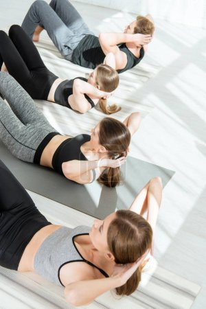 Photo for Overnead view of young women and man practicing yoga while doing press ups - Royalty Free Image