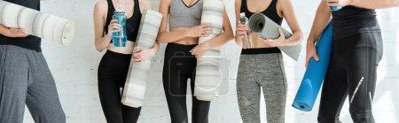 Photo pour Vue partielle des hommes et des femmes en vêtements de sport tenant des tapis de yoga et des bouteilles d'eau - image libre de droit