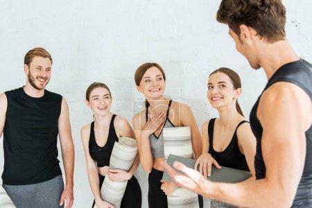 Photo pour Des amis joyeux discutent en tenant des tapis de yoga - image libre de droit