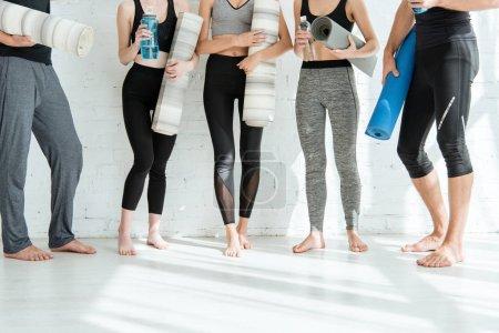 Ausgeschnittene Ansicht von Männern und Frauen in Sportbekleidung, die Yogamatten und Wasserflaschen in der Hand halten