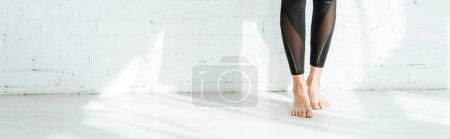 Photo for Cropped view of barefoot woman standing near white wall, panoramic shot - Royalty Free Image