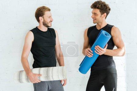 Photo pour Deux jeunes hommes souriants parlant en tenant des tapis de yoga - image libre de droit