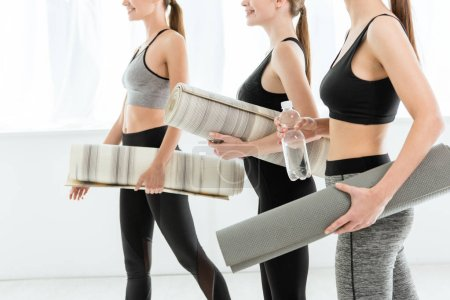 Photo pour Crochet vue de trois jeunes femmes tenant des tapis de yoga - image libre de droit