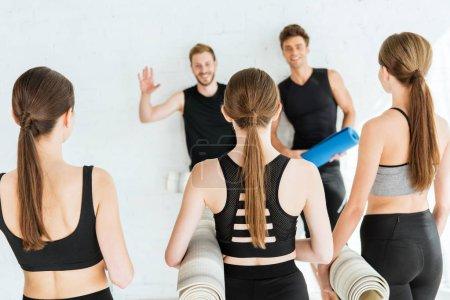Photo pour Un homme souriant agitant la main à des filles tenant des nattes de yoga - image libre de droit