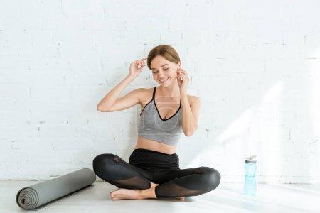 Foto de Jovencita alegre sentada en posición fácil y escuchando música en auriculares. - Imagen libre de derechos