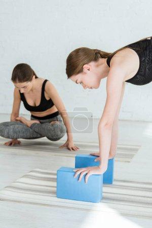 Photo pour Une jeune femme pratique le yoga en se penchant sur des tribunes avec les mains près d'une fille en hauteur pose - image libre de droit
