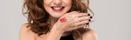 panoramic shot of cheerful girl with lipstick palette on hand isolated on grey