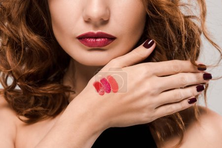 Photo pour Crochet vue de femme avec palette de rouge à lèvres à la main isolée sur grise - image libre de droit
