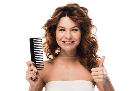 Photo pour Fille heureuse avec les cheveux bouclés tenant brosse à cheveux et montrant pouce isolé sur blanc - image libre de droit