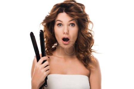 Photo pour Surprise fille bouclée tenant fer à cheveux isolé sur blanc - image libre de droit