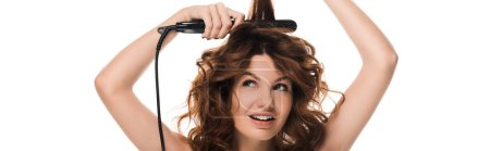panoramic shot of curly woman using hair straightener isolated on white