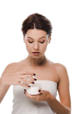 Photo pour Séduisante femme regardant récipient avec crème visage isolé sur blanc - image libre de droit