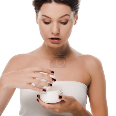 young woman looking at container with face cream isolated on white