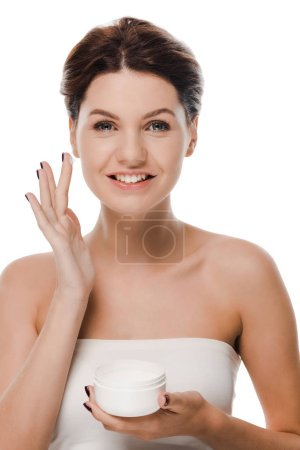 cheerful woman with face cream on finger looking at camera isolated on white