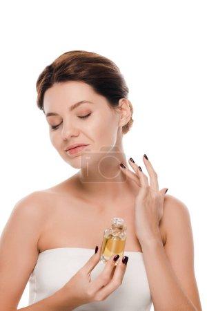 Photo pour Une femme joyeuse aux yeux fermés applique un parfum d'huile sur le cou isolé sur - image libre de droit