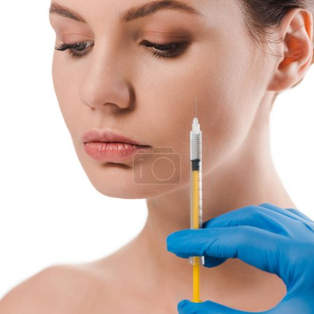 Photo pour Crochet vue d'un chirurgien en plastique dans un gant bleu en latex seringue près d'une séduisante femme nue isolée sur blanc - image libre de droit
