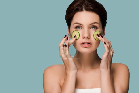 attractive woman touching cucumbers on face isolated on blue
