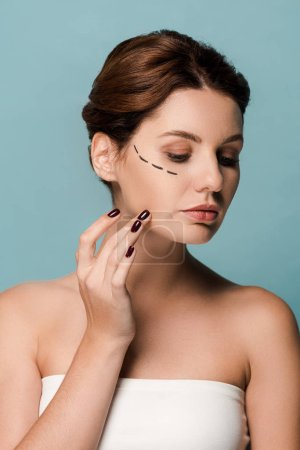 Photo pour Attractive woman touching face with marked lines isolated on blue - image libre de droit