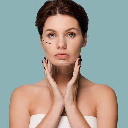 Photo pour Jeune femme attirante touchant le visage avec des lignes marquées isolées sur bleu - image libre de droit