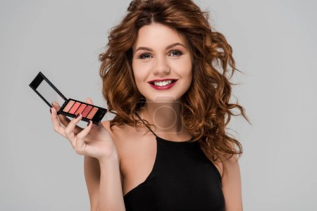 Photo for Happy curly woman holding set of lip gloss isolated on grey - Royalty Free Image
