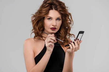 Photo pour Attractive curly woman holding cosmetic brush isolated on grey - image libre de droit