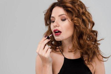 Photo pour Belle et frisée femme appliquer brillant aux lèvres isolé sur gris - image libre de droit