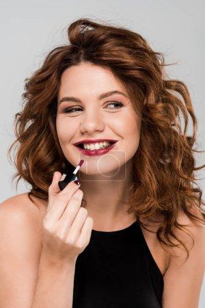 Photo pour Une femme heureuse et frisée applique un brillant aux lèvres isolé sur gris - image libre de droit