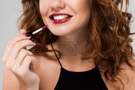 Photo pour Crochet vue d'une femme heureuse et frisée tenant un lustre de lèvre isolé sur gris - image libre de droit
