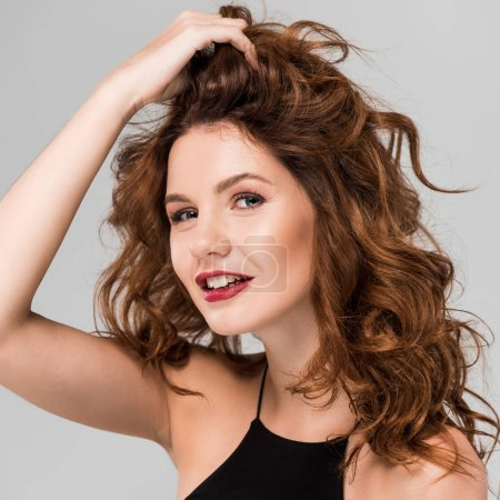 Photo for Cheerful woman touching curly hair isolated on grey - Royalty Free Image