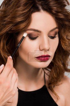 Foto de La vista recortada del artista maquillaje aplica sombra ocular sobre la mujer hermosa aislada en gris. - Imagen libre de derechos