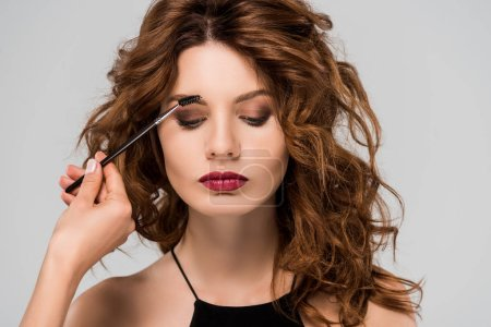 Photo for Cropped view of makeup artist styling eyebrows of beautiful woman isolated on grey - Royalty Free Image