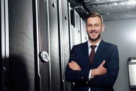Photo for Selective focus of cheerful businessman in suit and glasses standing with crossed arms in data center - Royalty Free Image