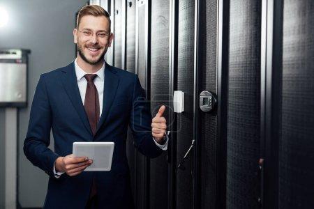 Photo pour Focalisation sélective d'un homme d'affaires gai tenant une tablette numérique et montrant son pouce dans un centre de données - image libre de droit