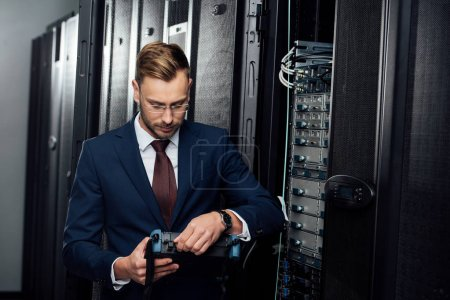 bearded businessman holding reflectometer in server room