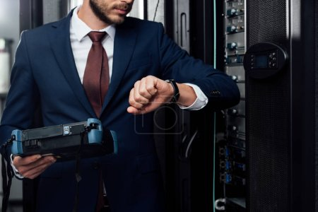 Photo for Cropped view of businessman standing with reflectometer and looking at watch in server room - Royalty Free Image