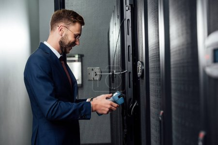 Photo pour Side view of happy business man standing with reflectometer in server room - image libre de droit