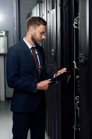 handsome businessman in suit holding clipboard and pen in data center