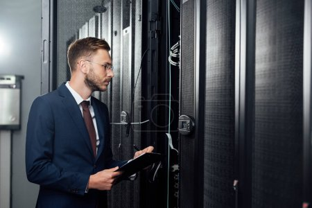 selective focus of handsome businessman in glasses and suit holding clipboard and pen in data center