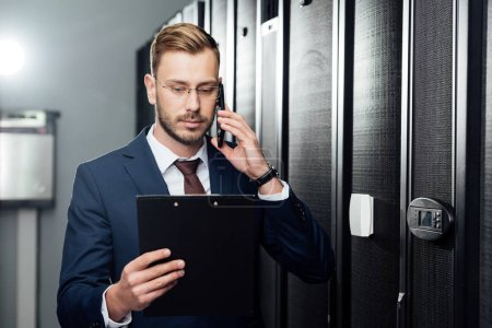 Photo for Handsome businessman talking on smartphone while looking at clipboard in server room - Royalty Free Image