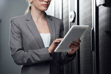 cropped view of businesswoman holding digital tablet in server room