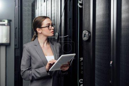 Photo pour Focalisation sélective d'une femme d'affaires en lunettes tenant une tablette numérique près des porte-serveurs - image libre de droit