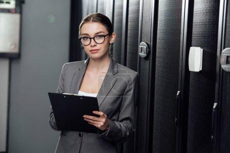 pretty businesswoman in glasses holding clipboard in data center