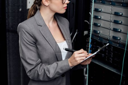 cropped view of businesswoman holding clipboard and pen in data center