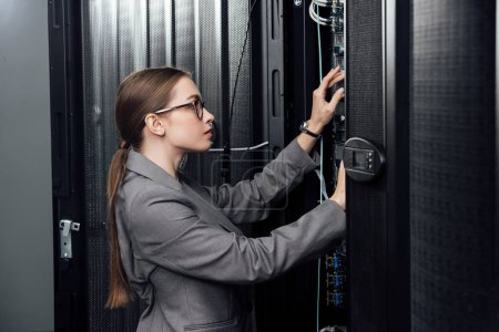 businesswoman in glasses looking at server rack in data center